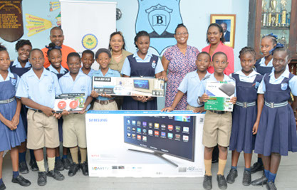 Fabian Chase, I.T. Co-ordinator (L) with students of Belmont Primary School and Director of BPWCCUL, Christina John